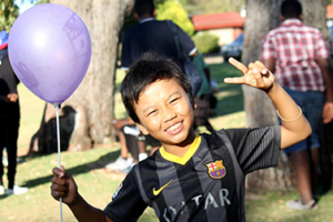 Boy with balloon gives peace sign